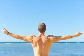 Muscular attractive man near the sea. Freedom concept.